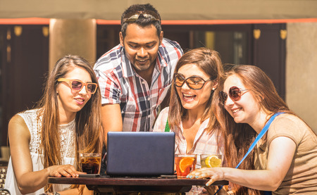 Multiracial friends at cocktail bar having fun with laptop - Connected community of young students people using pc on social media networks - Millennial generation concept sharing content online Stock Photo