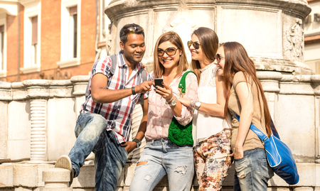 Multiracial friends using mobile smart phone at city tour - Happy friendship concept with student having fun together - Millenial people on peace love concept for no racism - Bright outside filter Stock Photo