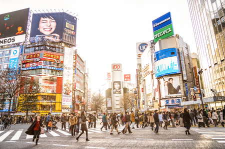 TOKYO - FEBRUARY 28, 2015: everyday life with commuters at rush hour on world famous Shibuya crossroad - International capital city with commercial ads in japanese language on landmark buildings