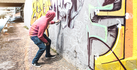 Street artist painting colorful graffiti on public wall - Modern art concept with urban guy performing and preparing live murales with multi color aerosol spray - Bright retro vintage filter 스톡 콘텐츠