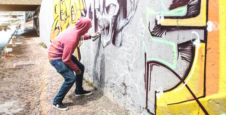 Straßenkünstler, der bunte Graffiti an der öffentlichen Wand malt - Modernes Kunstkonzept mit urbanem Kerl, der Live-Wandbilder mit mehrfarbigem Aerosolspray aufführt und vorbereitet - Heller Retro-Vintage-Filter