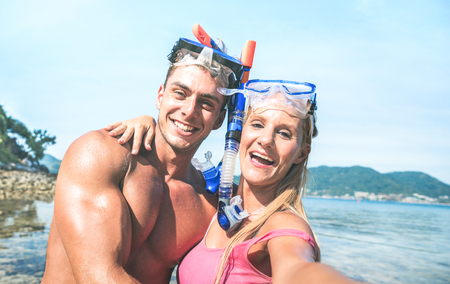 Young happy couple in love taking selfie in tropical excursion with water camera - Boat trip snorkeling in exotic scenarios - Youth lifestyle and travel concept around the world - Warm bright filter Imagens