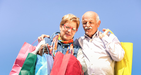 Senior couple shopping together with wife watching in husband bags - Elderly concept with mature man and woman having fun on sunny day - Happy retired people moments on vivid filter against blue sky
