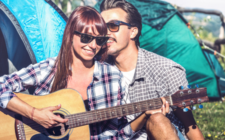 Lovers couple having fun outdoor cheering at camping place with vintage guitar - Young people enjoying summer time together in countryside - Youth travel friendship concept - Bright vintage filter Stock Photo
