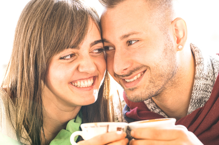 Young lovers couple at beginning of love story in coffee bar - Handsome man drinking cappuccino with pretty woman - Relationship concept with boyfriend and girlfriend at cafeteria - Warm bright filter Stock Photo