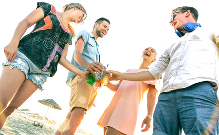 Happy millenial friends group having fun at beach party drinking fancy cocktails at sunset - Summer joy and friendship concept with young people millennials on luxury vacation - Warm sunshine filter