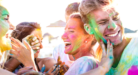 Happy friends having fun at beach party on holi colors festival event - Young people laughing together with candid excited mood at summer vacation - Youth friendship concept on vivid contrasted filter