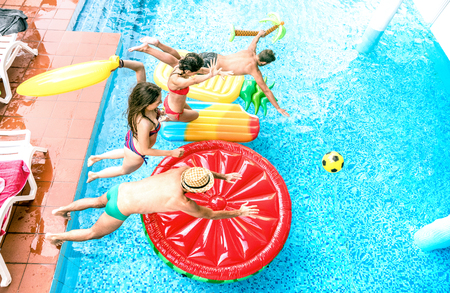 High angle view of millenial friends jumping at swimming pool party - Youth vacation concept with happy guys and girls having fun in summer day at luxury resort - Young people on warm bright filter Stock Photo