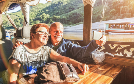 Senior retired couple of happy vacationers taking selfie at Mekong exploration tour with slowboat in Laos PDR - Active elderly travel concept on trip around the world - Warm saturated sunset filter