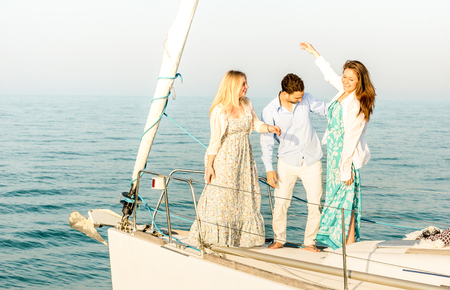 Best friends dancing and having fun on exclusive luxury sailing boat - Friendship travel concept with young people millenial sharing time together on party trip cruise - Bright color tone filter Stock Photo