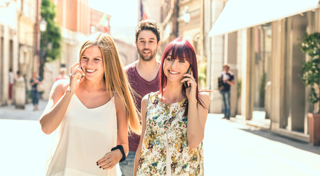 Young man following pretty women while having fun together on city street - Technology concept in everyday lifestyle with millenials people talking and using mobile smart phone - Bright filter Stock Photo