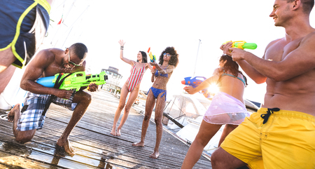 Multiracial happy friends having genuine fun with waterfight battle at summer location - Trendy vacation concept with young people millenials using water gun at beach docks - Warm backlight filter