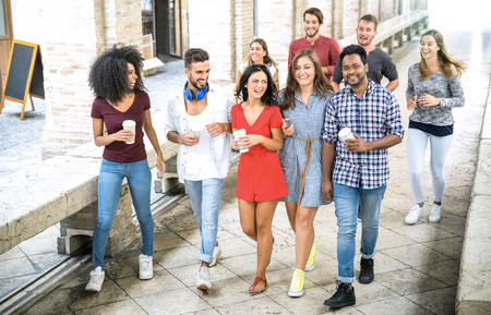 Multiracial friends group walking in city center - Happy guys and girls having fun around old town streets - University students on summer vacations after school end time - Bright daytime filter