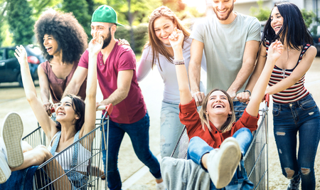Young multiracial people having fun together with shopping cart - Millenial friends sharing time with trolleys at commercial mall parking - Youth lifestyle concept with focus on girl with hands up Stock Photo