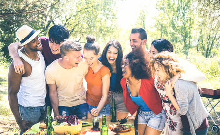 Happy friends having fun together at pic nic barbecue party - Young millenial people at picnic on open air festival - Youth friendship concept with guys and girls cheering at barbeque - Bright filter Stock Photo