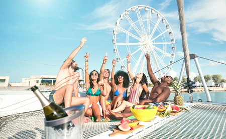 Multiracial friends having fun with wine and fruit brunch at sail boat party - Friendship concept with multi racial people on sailboat - Luxury travel lifestyle on happy vacation - Azure bright filter