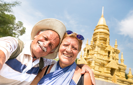 Senior couple taking selfie at golden temple in Ko Samui - Happy retired people traveling to Thailand wonders - Active elderly concept and fun around the world to south east asia destinations
