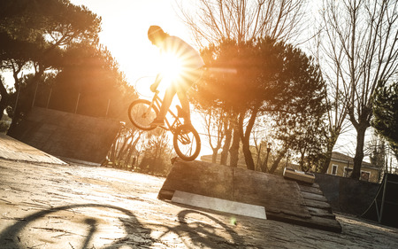 Urban athlete biker performing acrobatic jump at public park - Guy riding bmx bicycle at extreme sport competition on sunny afternoon - Alternative lifestyle concept on warm sunset sunshine filter
