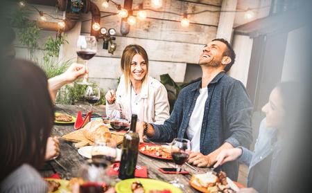 Jeunes amis s'amusant à boire du vin rouge sur le balcon lors d'un dîner à la maison - Des gens heureux qui mangent de la nourriture pour barbecue dans un restaurant alternatif chic ensemble - Concept de style de vie sur filtre désaturé