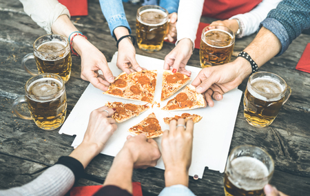 Millenial friends group drinking beer and sharing pizza slices at bar restaurant - Friendship concept with young people having fun together eating snack at risto pub pizzeria - Vintage contrast filter