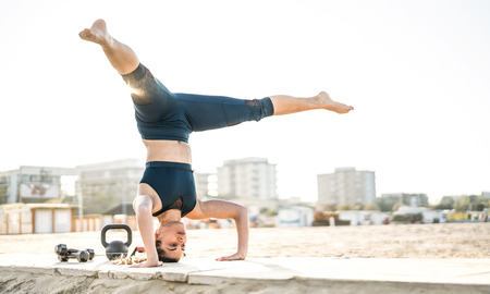 Portrait of athletic woman exercising calisthenic balance move at outdoors beach location - Modern alternative work out and body care concept in urban sport environment - Bright desaturated filter