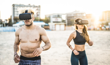 Young couple running at beach with virtual reality goggles headset - Sport and technology concept with friends jogging and exercising on trek simulation on summer time - Contrast sunset filter