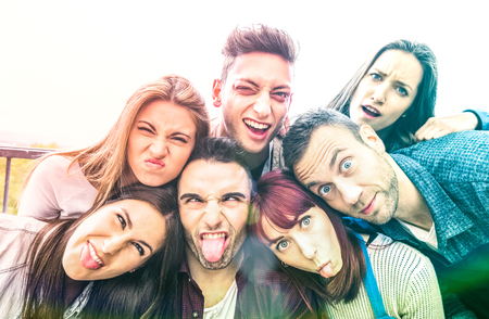 Multicultural millenial friends taking selfie with funny faces - Happy youth friendship concept with millennial young trendy people having fun together with tongue out -  Bright multicolor filter Stok Fotoğraf