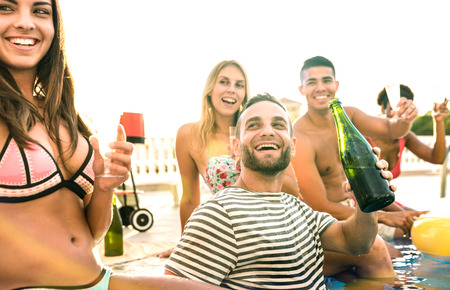 Cropped view of happy friends people drinking white wine champagne at swimming pool party - Vacation concept with young guys and girls having fun in summer day at luxury resort - Warm vintage filter Stok Fotoğraf