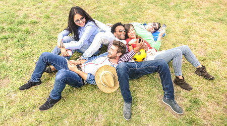 Multiracial best friends having fun at meadow picnic - Happy friendship fun concept with young people millenials sharing time together with mobile phone on spring summer time - Bright afternoon filter