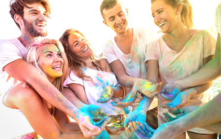 Young friends having fun at beach party on holi colors festival - Happy people playing together with genuine carefree mood at summer event - Youth friendship concept with multi colored sunshine filter
