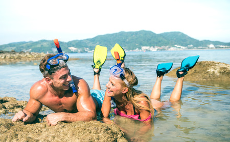 Happy couple of vacationer in love having fun at water on tropical beach in Thailand with snorkel mask and fins - Active youth travel concept around the world - Warm bright day filtered color tones Stok Fotoğraf