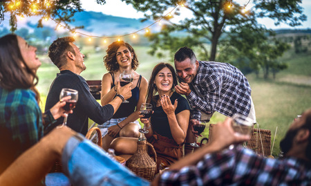 Young friends having fun at vineyard after sunset - Happy people millennial camping at open air pic nic under bulb lights - Youth friendship concept with guys and girls drinking wine at barbeque party Reklamní fotografie