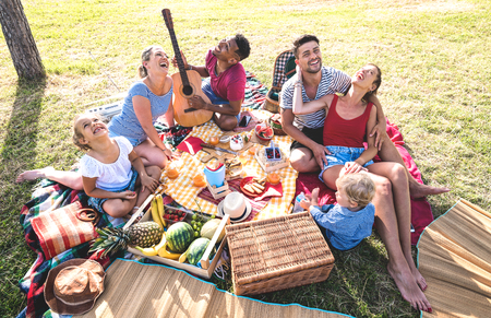 High angle top view of happy families having fun with kids at pic nic barbecue party - Multiracial love concept with mixed race people playing with children at public park - Warm retro vintage filter 스톡 콘텐츠