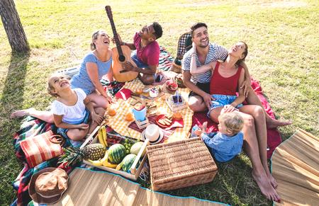 Hoge hoek bovenaanzicht van gelukkige gezinnen die plezier hebben met kinderen op pic nic barbecue party - Multiraciale liefde concept met gemengd ras mensen spelen met kinderen in openbaar park - Warm retro vintage filter