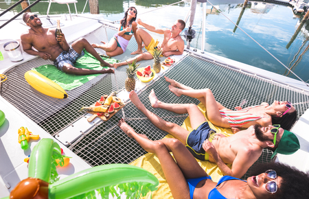 Amici felici multirazziali che si divertono rilassandosi alla festa in barca a vela - Concetto di amicizia con persone multirazziali su catamarano a vela - Viaggio di lusso e concetto di vacanza esclusiva - Filtro luminoso vivido