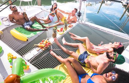 Gemischtrassige glückliche Freunde, die sich auf der Segelbootparty entspannen - Freundschaftskonzept mit multiethnischen Menschen auf einem Katamaran-Segelboot - Luxusreisen und exklusives Urlaubskonzept - Lebendige helle Filter