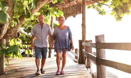 Happy senior couple walking holding hand at Koh Phangan beach promenade - Active elderly and travel lifestyle concept with retired mature people at Thailand luxury resort - Bright warm day filter