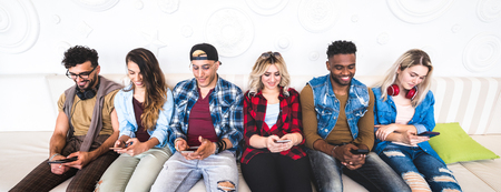 Friends using smartphone on sofa at indoor venue - People group addicted by mobile smart phone - Technology concept with always connected millennials sharing content online - Bright vivid filter