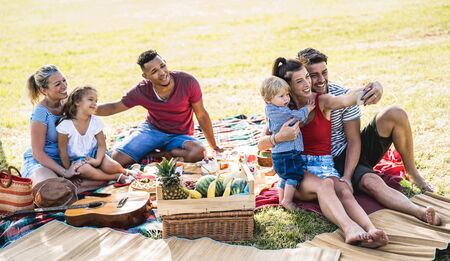 Happy multiracial families taking selfie at pic nic garden party - Multicultural joy and love concept with mixed race people having fun together picnic barbecue before sunset - Warm bright filter Imagens