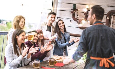 Young friends having fun drinking beer on balcony at house dinner party - Happy people eating pizza at fancy alternative restaurant together - Dining lifestyle concept on bright sunshine filter