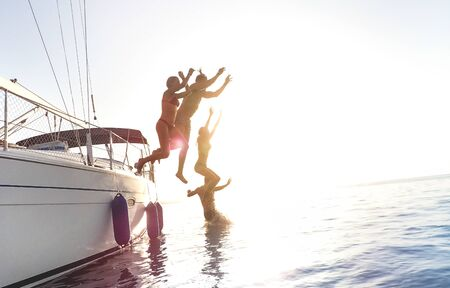 Side view of young millennial friends jumping from sailboat on sea ocean trip - Guys and girls having summer fun together at sail boat party day - Luxury excursion concept on vivid contrasted filter