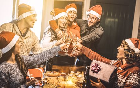 Friends group with santa hats exchanging Christmas presents with champagne wine toast at home dinner - Winter holiday concept with young people enjoying time and having fun together - Focus on glasses