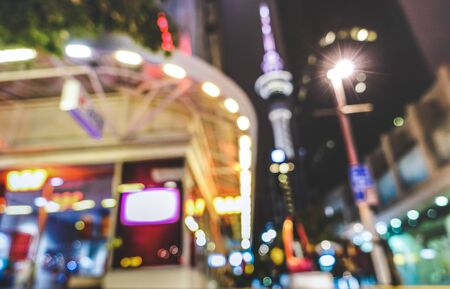 Blurred defocused view of urban nightscape at city center in Auckland capital of New Zealand - Abstract bokeh background by night with glowing lights and blurry buildings - Vivid colors filter Stock Photo