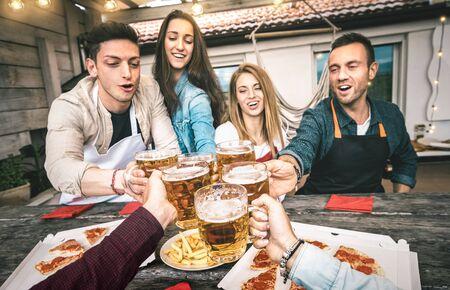 Punto de vista de jóvenes amigos comiendo pizza para llevar en el patio de la casa después del trabajo - Concepto de amistad con gente feliz disfrutando del tiempo juntos y divirtiéndose bebiendo pintas de cerveza - Concéntrese en vasos de cerveza