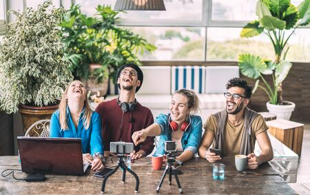 Jóvenes amigos milenarios que comparten contenido creativo en línea - Concepto de marketing digital con influencer de próxima generación divirtiéndose en el aire con transmisión de video por radio - Tiempo de vlogging en el espacio de coworking de inicio