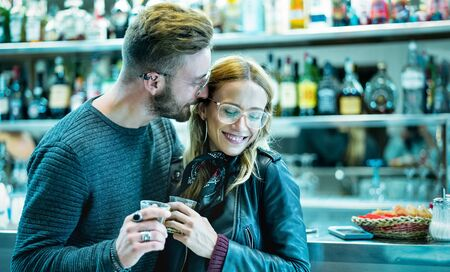 Young couple at beginning of love story in cocktail bar - Handsome man drinking coffee with nice woman - Relationship concept with boyfriend and girlfriend having drunk fun together - Cold neon filter Stock Photo