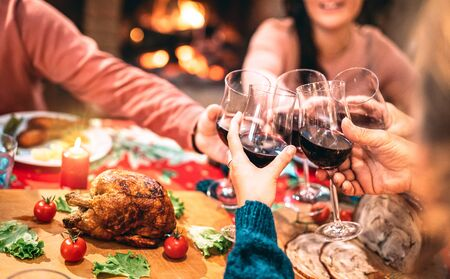Family toasting red wine and having fun at Christmas supper party - Holiday celebration concept with happy people enjoying winter time together at home dinner fest - Warm filter with focus on glasses
