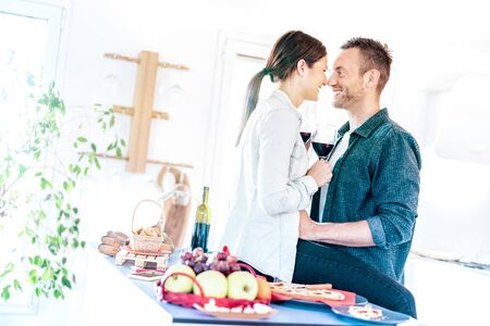 Young couple toasting red wine and almost kissing at home kitchen - Happy millenial lovers enjoying tender moment cheering together at jubilee anniversary - Genuine love concept on bright azure filter Reklamní fotografie - 133202740