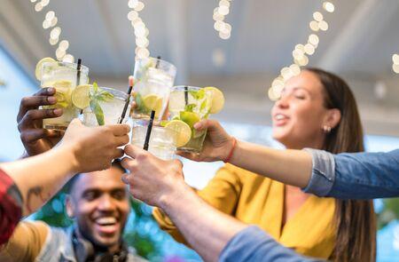 Beste vrienden die samen drinken in het modebar-restaurant - Vriendschapsconcept met jonge mensen die plezier hebben met het roosteren van drankjes op happy hour in de pub - Levendig neonfilter met focus op mojito-cocktails