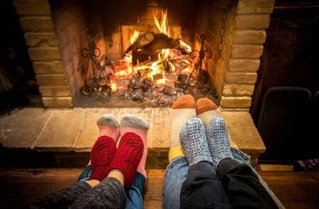 Mother father and kids sitting at cosy fireplace on Christmas time - Lovely family resting together on woolen socks at home fire place - Winter holiday and x mas concept on comfy warm flame filter